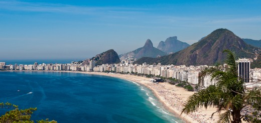 Scenic view of Copacabana beach with buildings in the front and mountains behind.